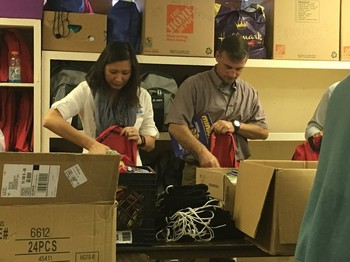 PDA Advisory Committee members Kathy Lee-Cornell and Jeff Holland pack backpacks at the IWC center in San Antonio