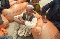 Man with relief supplies in orange bags