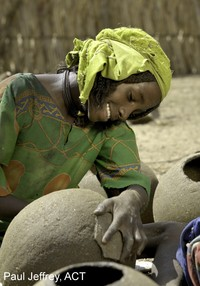 girl working with water jugs; photo by Paul Jeffrey, ACT