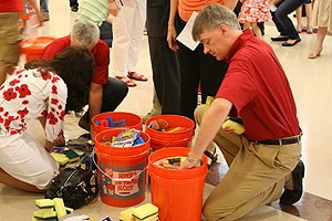 man filling orange bucket with supplies; photo by Preston Hollow PC
