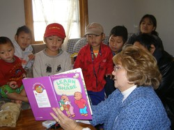 adult reading a book to children