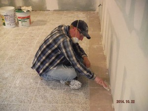 Dan sitting on floor working with drywall tool