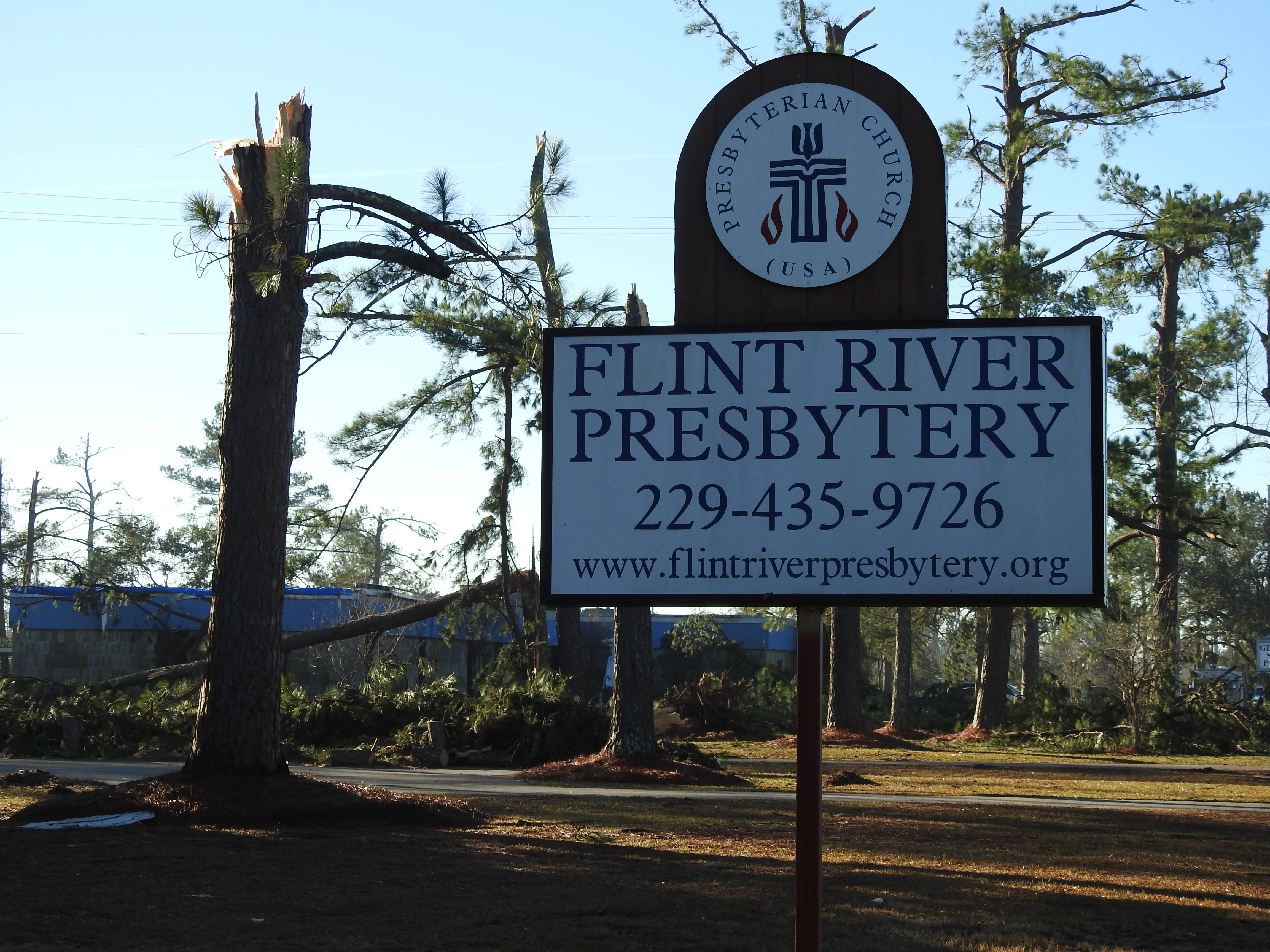 a damaged tree next to the sign for Flint River Presbytery