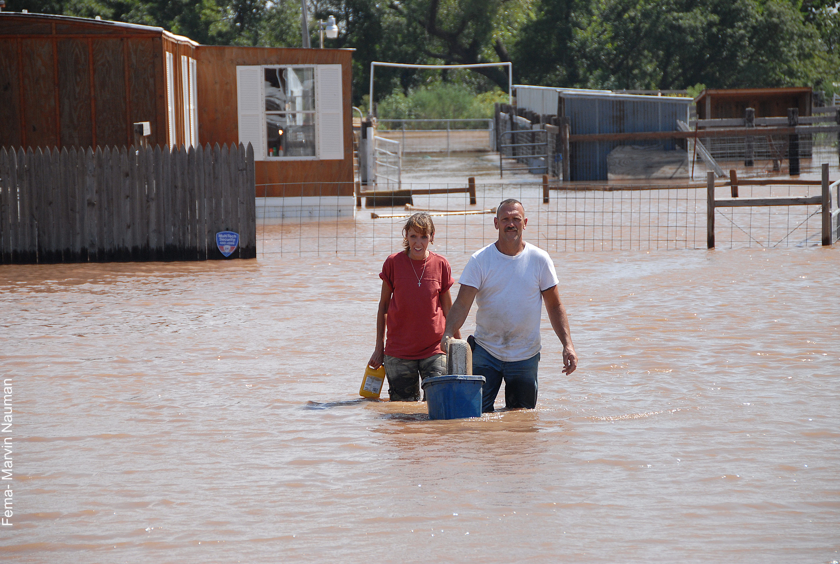 couple walking rhough flood waters
