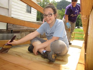 youth volunteer stains a deck