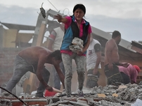 Ecuadorean Veronica Paladines, removes rubble in search for her husband at Tarqui neigbourhood in Manta, Ecuador on April 17, 2016 a day after a powerful quake hit the country.