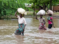 Women wade in the water carrying supplies on their heads