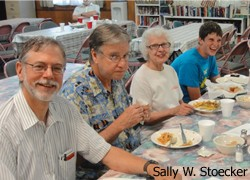 four volunteers eating at a table; photo by Sally W. Stoecker