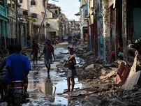 A girl walks on a street damaged in hurricane Matthew, in Jeremie, in western Haiti, on October 7, 2016. The full scale of the devastation in hurricane-hit rural Haiti became clear as the death toll surged over 400, three days after Hurricane Matthew leveled huge swaths of the country's south.