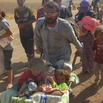 Iraqi man fleeing with children in wheelbarrow; Learn more about the response in Iraq