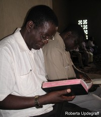 man looks at Bible; photo by Roberta Updegraff