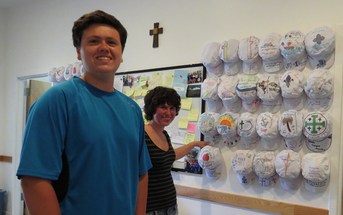 two people standing by four rows of hats hanging on wall