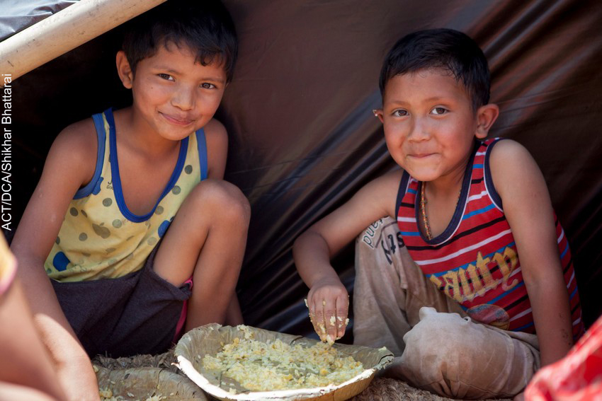 Young boys in temporary shelter enjoy a meal provided by ACT Alliance partners in Nepal