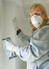 woman wearing mask and working with drywall