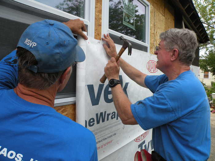 volunteers hammering insulation to side of house