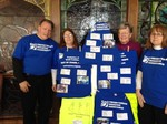volunteers standing by blue tshirts with tags showing mission locations