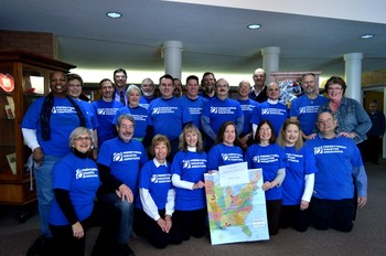 volunteer team wearing blue shirts with U.S. map in front of them