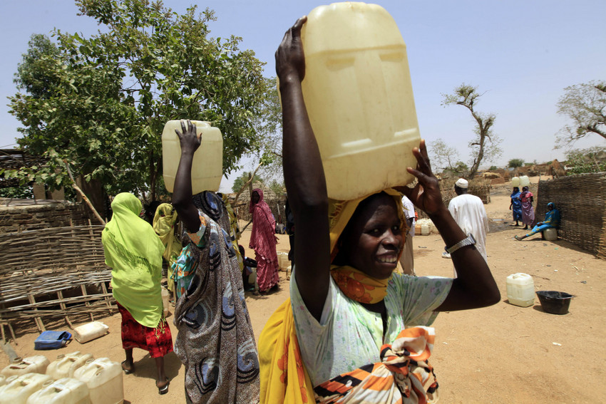 Women carry water containers from a water point at Deleij camp near Garsila, West Darfur
