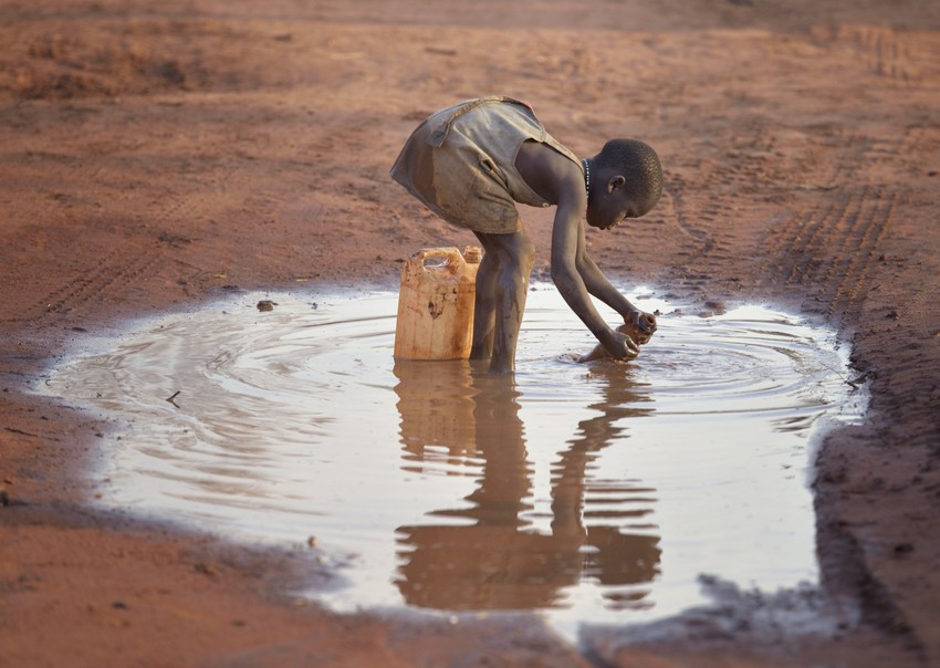 A girl fills a container with muddy water in the Ajuong Thok Refugee Camp in South Sudan