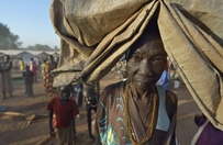 A woman carries her tarp early in the morning in a camp for over 5,000 internally displaced persons in an Episcopal Church compound in Wau, South Sudan. Most of the families here were displaced by violence early in 2017, after a larger number took refuge in other church sites when widespread armed conflict engulfed Wau in June 2016. Most of the people in this camp have no shelter, and use a tarp or mats to lay on the ground at night.