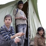 children in front of tent; Learn more about the response in Syria