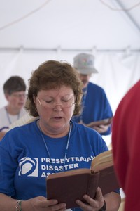 woman sings from hymnbook; photo by Barry Carlin