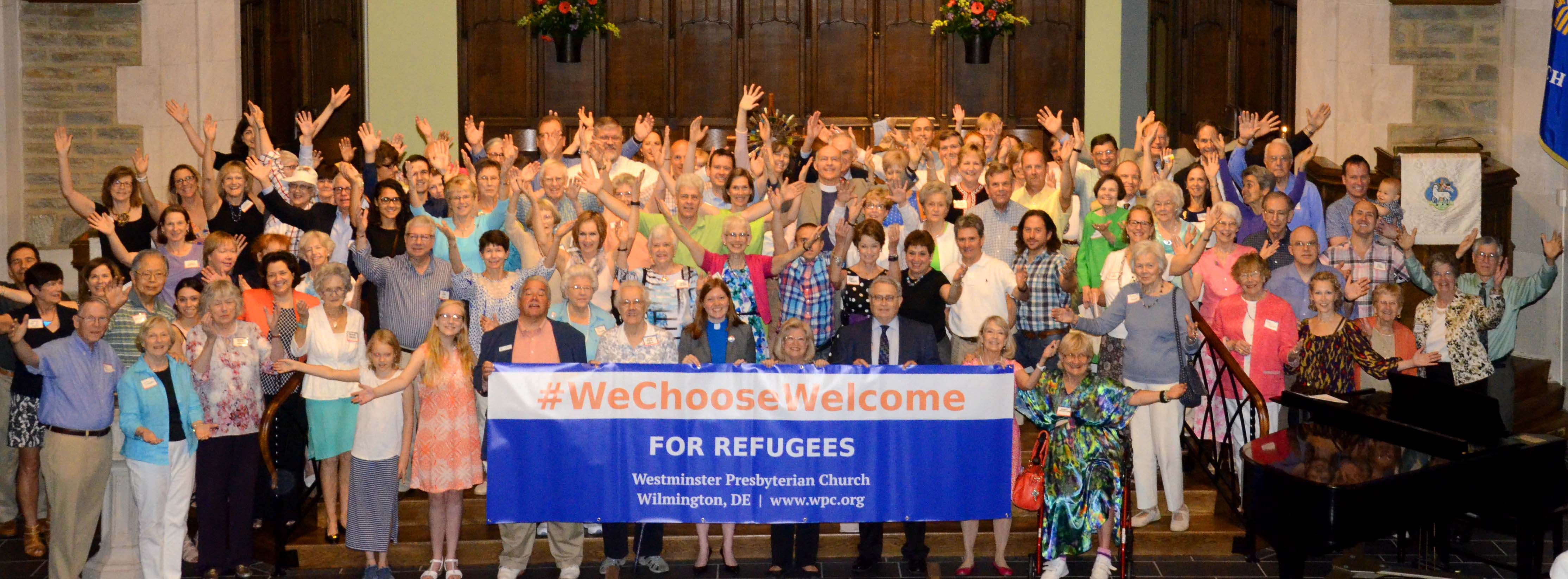 "Members of Westminster Presbyterian Church in Wilmington, Delaware stand behind a banner that reads ""We Choose Welcome for refugees"""